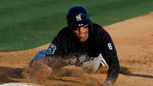 New York Yankees' Robert Refsnyder dives back to first base on a pick off attempt in the fourth inning of a spring training baseball game against the Washington Nationals, Wednesday, March 23, 2016, in Viera, Fla.