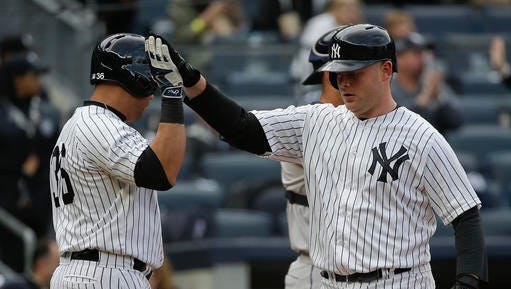 New York Yankees' Brian McCann, right, is greeted by Carlos Beltran (36) after hitting a solo home run against the Houston Astros during the fourth inning of a baseball game, Thursday, April 7, 2016, in New York.