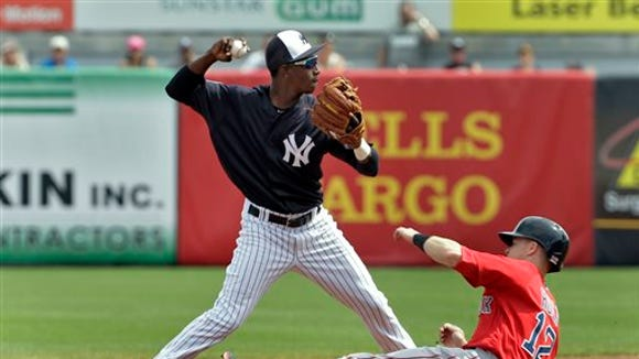 New York Yankees shortstop Jorge Mateo forces Boston Red Sox's Brock Holt (12) at second base and turns a double play on Boston's Travis Shaw during the first inning of a spring training baseball game Saturday, March 5, 2016, in Tampa, Fla.