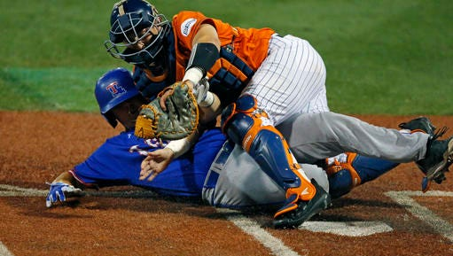 Louisiana Tech's Jonathan Washam is tagged out by Cal State Fullerton catcher Chris Hudgins while trying to steal home in the fourth inning during their NCAA Regional Baseball Tournament game at Dudy Noble Field in Starkville, Miss., Friday.