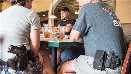 Jeff Coursey, of Paris, Texas, center, sits in a restaurant July 9, 2016. Coursey is considering starting a local chapter of Open Carry Texas, which supports the right to openly carry a firearm in public. Seated at the table with him are Bill Wilson, owner of Wilson Combat, an Arkansas gunmaker, and his wife, Joyce Wilson, executive director of the International Defensive Pistol Association.