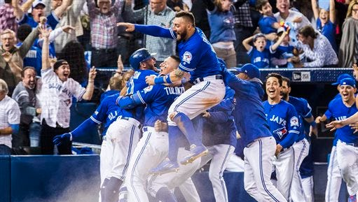 Toronto Blue Jays players celebrate their walk-off win to eliminate the Texas Rangers during the tenth inning to win the American League Division Series in Toronto on Sunday, Sunday, Oct. 9, 2016.
