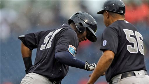 New York Yankees' Miguel Andujar, left, is greeted by third base coach Tony Pena after hitting a two-run home run off Philadelphia Phillies starting pitcher Brett Oberholtzer during the fourth inning of a spring training baseball game Tuesday, March 29, 2016, in Clearwater, Fla.