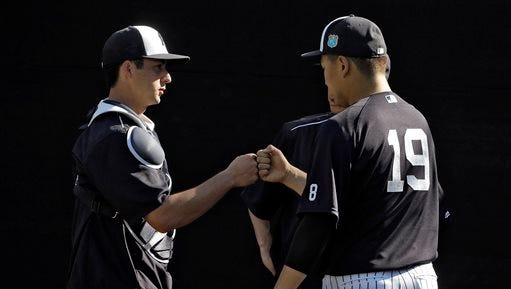 New York Yankees pitcher Masahiro Tanaka, of Japan, right, fist bumps catcher Kyle Higashioka after throwing a bullpen session during a spring training baseball workout Monday, Feb. 22, 2016, in Tampa, Fla.