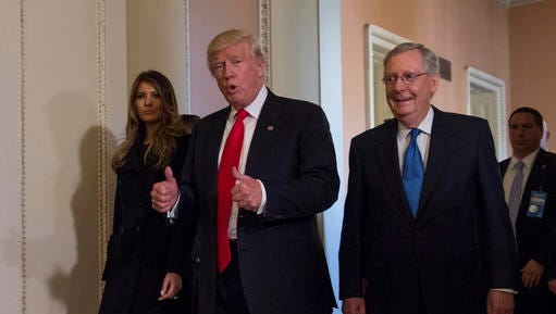President-elect Donald Trump, flanked by his wife Melania and Senate Majority Leader Mitch McConnell of Ky., gives a thumbs-up while walking on Capitol Hill in Washington, Thursday, Nov. 10, 2016, after their meeting.  (AP Photo/Molly Riley)