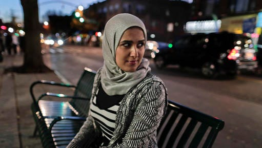 "Enas Almadhwahi, an immigration outreach organizer for the Arab American Association of New York, sits for a photo along Fifth Avenue in the Bay Ridge neighborhood of Brooklyn, Friday, Nov. 11, 2016, in New York. The 28-year-old Yemeni immigrant who has been in the U.S. since 2008, became a citizen in 2016 and voted for the first time. To mark the occasion, she brought her 7-year-old daughter, along with some co-workers. ""At that moment, I was so happy,"" she said. The next day, when she told her daughter Trump had won, the girl cried. (AP Photo/Julie Jacobson)"