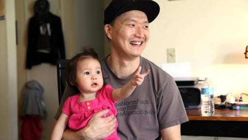 FILE - In this March 19, 2015, file photo, Korean adoptee Adam Crapser poses with daughter, Christal in the family's living room in Vancouver, Wash. The immigration attorney for Crapser, who was adopted from South Korea almost four decades ago and flown to America, says he has been deported. U.S. Immigration and Customs Enforcement ordered Adam Crapser be deported because of criminal convictions including assault and being a felon in possession of a weapon.