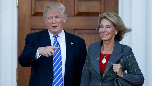 FILE - In this Nov. 19, 2016 file photo, President-elect Donald Trump and Betsy DeVos pose for photographs at Trump National Golf Club Bedminster clubhouse in Bedminster, N.J. Trump has chosen charter school advocate DeVos as Education Secretary in his administration.