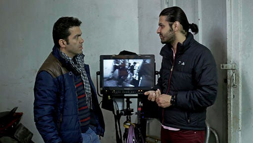 """In this undated photo provided by Iranian filmmaker Keywan Karimi, the director of photography Amin Jafari, left, speaks with Karimi during a scene of the movie called """"Drum"""", Tehran, Iran. Iranian filmmaker Keywan Karimi's production company says he has begun serving a year-long jail sentence handed down over footage deemed insulting by authorities."""