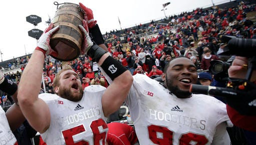 FILE - In this Nov. 28, 2015, file photo, Indiana defensive linemen Nick Mangieri (56) and Adarius Rayner (99) celebrate with the Old Oaken Bucket after defeating Purdue in an NCAA college football game in West Lafayette, Ind. Big Ten teams have been playing for buckets, bronzed pigs, jugs and more since around the turn of the 20th century. It's all a part of Midwestern football lore, and there's nothing like watching jubilant winners sprint to claim their prize when time expires. (AP Photo/AJ Mast, File)