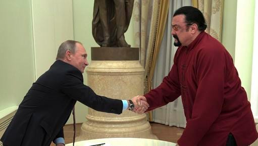 Russian President Vladimir Putin shakes hands with U.S. actor Steven Seagal in the Kremlin in Moscow,Friday, Nov. 25, 2016. Putin has given a Russian passport to Seagal, a regular visitor to Russia in recent years, calling it a sign of a thaw in relations between the two countries.