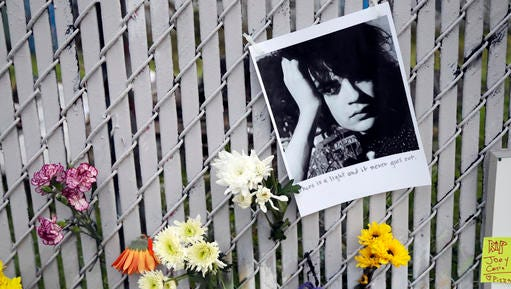 Pictures and flowers adorn a fence near the site of a warehouse fire Monday in Oakland, Calif. The death toll in the Oakland warehouse fire climbed Monday with more bodies still feared buried in the blackened ruins, and families anxiously awaited word of their missing loved ones. (AP Photo/Marcio Jose Sanchez)
