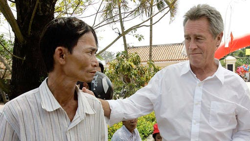 FILE - In this Saturday, March 15, 2008 file photo, My Lai Massacre survivor Do Ba, 48, left, stands with former U.S. Army officer Lawrence Colburn, 58, right, who rescued him during the March 16, 1968 My Lai massacre, during the 40th anniversary of the incident in My Lai, Quang Ngai Province, Vietnam. Colburn, the helicopter gunner who helped end the slaughter of hundreds of unarmed Vietnamese villagers by American troops during the Vietnam War, died on Tuesday, Dec. 13, 2016. He was 67.