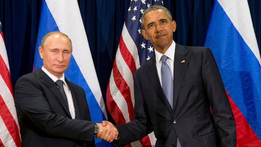 FILE - In this Monday, Sept. 28, 2015 file photo, U.S. President Barack Obama, right, and Russia's President President Vladimir Putin pose for members of the media before a bilateral meeting at the United Nations headquarters. President Barack Obama is promising that the U.S. will retaliate against Russia for its suspected meddling in America's election process, an accusation the Kremlin has vehemently denied.
