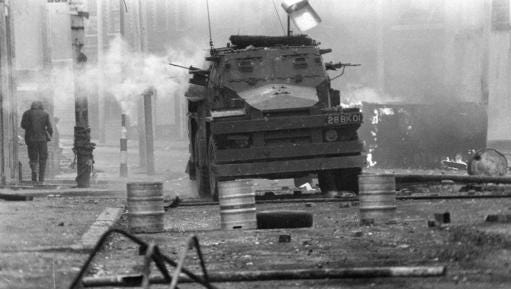 FILE - In this April 17, 1972 file photo, a British Army armoured vehicle makes its way along a barricade while on patrol in the Lower Falls area of west Belfast. Trouble in the area erupted after the shooting of Joe McCann, an IRA leader, the previous day. Belfast prosecutors say Friday Dec. 16, 2016, they will pursue murder charges against two retired British soldiers who fatally shot 25-year-old Joe McCann, a commander of the outlawed Official IRA faction.