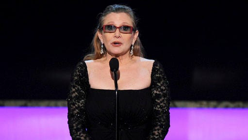 FILE - In this Sunday, Jan. 25, 2015 file photo, Carrie Fisher presents the life achievement award on stage at the 21st annual Screen Actors Guild Awards at the Shrine Auditorium in Los Angeles. Fisher has reportedly been transported to a hospital after suffering a severe medical emergency on a flight Friday, Dec. 23, 2016.