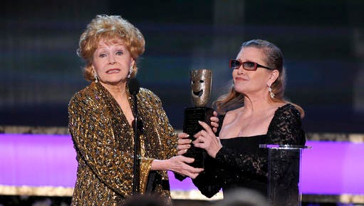 """FILE- In this Jan. 25, 2015, file photo, Carrie Fisher, right, presents her mother Debbie Reynolds with the Screen Actors Guild life achievement award at the 21st annual Screen Actors Guild Awards at the Shrine Auditorium in Los Angeles. """"La La Land"""" star Ryan Gosling thanked Reynolds at the Palm Springs Film Festival on Monday, Jan. 2, 2017, for serving as an inspiration to the cast and crew of the film."""