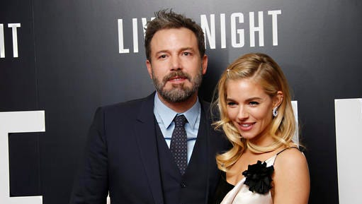 Actors Ben Affleck and Sienna Miller pose for photographers upon arrival at the premiere of the film 'Live By Night' in London, Wednesday, Jan. 11, 2016.