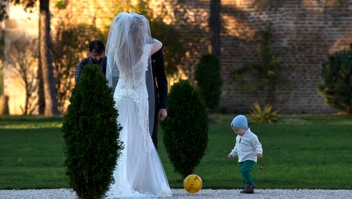 FILE - In this Nov. 9, 2013 file photo, a child plays with a ball next to a couple posing for a photographer in a park outside Bucharest, Romania. Newlywed couples took advantage of the unusual warm weather for the month of November, with temperatures reaching 20 degrees Celsius (68 degrees Fahrenheit), for outdoor photo sessions. Kiss goodbye some of those postcard-perfect, ideal-for-outdoor-wedding days. A new study said global warming is going to steal some of those exceedingly pleasant weather days from our future. On average, Earth will have four fewer days of mild and mostly dry weather by 2035 and ten fewer of them by the end of the century, according to a first-of-its-kind projection of nice weather.