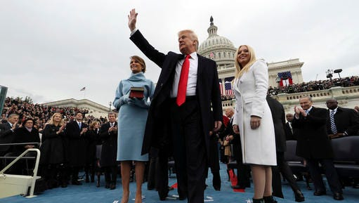 President Donald Trump waves after taking the oath of office as his wife Melania holds the Bible, and Tiffany Trump looks out to the crowd, Friday, Jan. 27, 2017 on Capitol Hill in Washington.