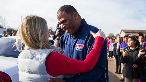 UPDATES TO SAY HE FAKED HAVING CANCER- In this Jan. 20, 2017 photo, first-year teacher's aid Kevin MaBone talks to principal Leslie Feinglas as he is surprised with a car during a presentation by students and teachers outside Wilkinson Middle School in Mesquite, Texas. Hundreds of MaBone's new friends at Wilkinson lined a muddy parking lot to leave their impression on him. MaBone told the school he was diagnosed with cancer in December and was relying on staff to get to work and medical appointments after his car broke down. However, officials said Tuesday, Jan. 24, 2017, that he faked having cancer and his time off granted for surgery coincided with a West Virginia court date. (Ashley Landis/The Dallas Morning News via AP)