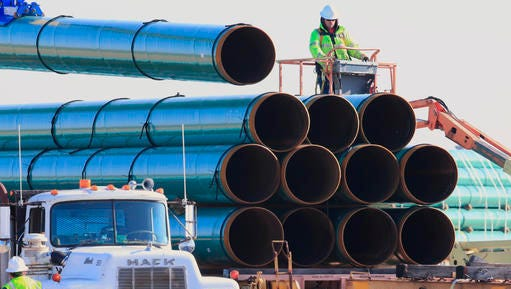 FILE - In this May 9, 2015, file photo, workers unload pipes for the proposed Dakota Access oil pipeline that would stretch from the Bakken oil fields in North Dakota to Illinois. The Dakota Access project, which is mostly completed, has created about 12,000 construction jobs, according to project leader Energy Transfer Partners LP. Most of those jobs are over, however.