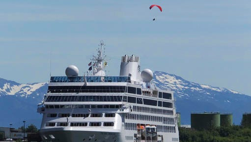 FILE - This June 26, 2014, file photo, shows a cruise ship docked in Juneau, Alaska, while a paraglider soars above. Alaska expects 1.06 million cruise passengers this year, breaking its 2008 record of 1.03 million visits. The Alaska Travel Industry Association says larger ships are bringing more visitors, and destinations like Sitka, Juneau and Icy Strait Point have built out piers to accommodate bigger vessels. Smaller ships are simultaneously expanding service, specializing in more remote destinations the bigger ships can't reach.