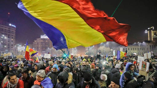 A man waves a large Romanian flag during a protest joined by tens of thousands against a government decree that dilutes what qualifies as corruption, in Bucharest, Romania, Thursday, Feb. 2, 2017. Huge protests erupted in the capital and spread to cities around Romania in the past two nights after the government changed the law — one of the biggest protests in Romania since communism ended in 1989.