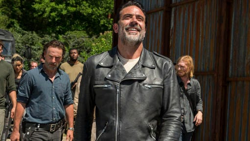 """This image released by AMC shows Jeffrey Dean Morgan as Negan, foreground,from the series, """"The Walking Dead."""" The popular zombie series makes its midseason return Sunday on AMC."""