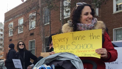 Jennifer Ibrahim participates in a demonstration outside Jefferson Middle School in Washington, Friday, Feb. 10, 2017, as Education Secretary Betsy DeVos paid her first visit as education secretary in a bid to mend fences with educators after a bruising confirmation battle.