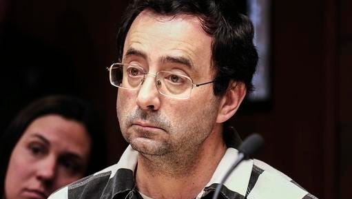FILE - In this Friday, Feb. 17, 2017, file photo, Dr. Larry Nassar listens to testimony of a witness during a preliminary hearing, in Lansing, Mich. The former sports doctor at Michigan State University who specialized in treating gymnasts has been charged with sexual assault. Dr. Nassar was charged Wednesday, Feb. 22,  in two Michigan counties. Online records show he's facing nine charges in Ingham county, including first-degree criminal sexual conduct against a victim under age 13. Nassar had a clinic at Michigan State, where he treated members of the gymnastics team and younger regional gymnasts.