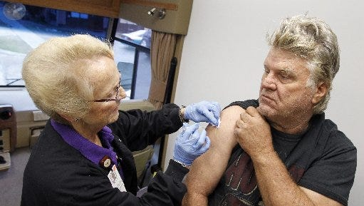 Registered Nurse Paula Bugay gives Richard Roll a flu shot Tuesday, Jan. 15, 2013, inside the Christus Spohn Hospital's mobile clinic parked outside of the Salvation Army shelter in Corpus Christi.