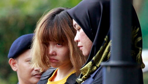Vietnamese suspect Doan Thi Huong, center, in the ongoing assassination investigation, is escorted by police officers out from Sepang court in Sepang, Malaysia on Wednesday, March 1, 2017. Appearing calm and solemn, two young women accused of smearing VX nerve agent on Kim Jong Nam, the estranged half brother of North Korea's leader, were charged with murder Wednesday.