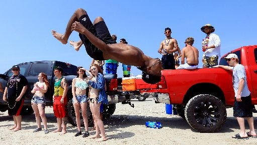 Beach-goers party and dance to music on the back of a pickup during spring break Monday, March 14, 2016, in Port Aransas.