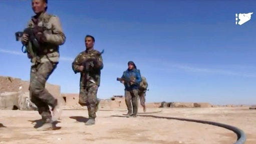 FILE - This file frame grab from a video provided on Monday, March 6, 2017 by the Syria Democratic Forces (SDF), shows fighters from the SDF running during fighting with Islamic State group militant, in Raqqa's eastern countryside, Syria. The Kurdish-led Syrian Democratic Forces is likely to lead the operation to capture the northern Syrian city of Raqqa from the Islamic State group in the coming weeks as the forces presses in its offensive against the extremists in areas close to their de facto capital.