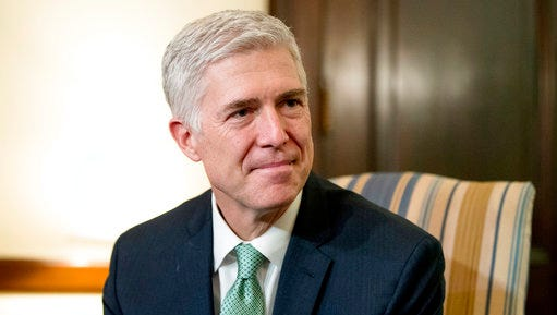 """FILE - In this Feb. 14, 2017, file photo, Supreme Court Justice nominee Neil Gorsuch meets with Sen. Chris Coons, D-Del. on Capitol Hill in Washington. Gorsuch is roundly described by colleagues and friends as a silver-haired combination of wicked smarts, down-to-earth modesty, disarming warmth and careful deliberation. His critics largely agree with that view of the self-described """"workaday judge"""" in polyester robes. Even so, they're not sure it's enough to warrant giving him a spot on the court."""