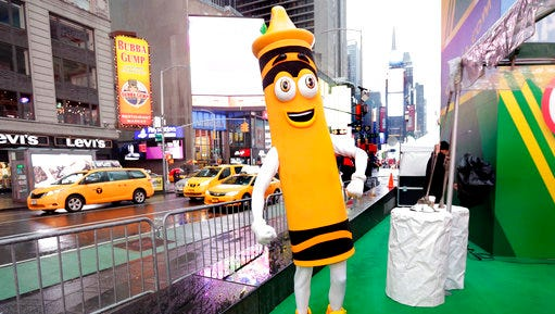 "A dandelion crayon character poses for photos during a Crayola event in New York's Times Square, Friday, March 31, 2017. Crayola announced Friday, National Crayon Day, that it's replacing the color dandelion in its 24-pack with a crayon in ""the blue family."""
