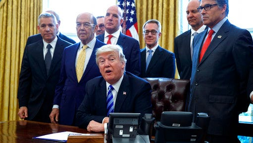 FILE - In this March 24, 2017, file photo, President Donald Trump announces the approval of a permit to build the Keystone XL pipeline, clearing the way for the $8 billion project in the Oval Office of the White House in Washington. From left are, TransCanada CEO Russell K. Girling, Commerce Secretary Wilbur Ross and Energy Secretary Rick Perry. Amid staff turmoil and shake-ups, travel bans blocked by federal courts and the Russia cloud hanging overhead, Trump is plucking away at another piece of his agenda: undoing Obama.