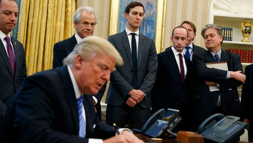 FILE - In this Jan. 23, 2017 file photo, White House chief strategist Steve Bannon, right, and others, watch as President Donald Trump signs an executive order in the Oval Office of the White House in Washington. President Donald Trump is distancing himself from chief strategist Steve Bannon, a move that has Bannon's friends and allies worried the White House is about to lose its most important populist voice.