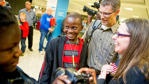 FILE - In this Wednesday, Nov. 11, 2015 file photo, Jennifer and Eric Sands of Illinois, right, accompanied by their adopted daughter Joy, 12, left, smile as their adopted son Issaac, 12, center arrives from the Congo at Dulles International Airport in Dulles, Va. According to State Department figures released on Thursday, April 13, 2017, the number of foreign children adopted by U.S. parents dropped almost 5 percent in 2016, continuing a steady decline that's now extended for 12 years.