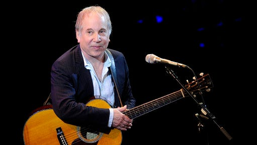 "FILE - In this April 2, 2012 file photo, singer Paul Simon performs at ""A Celebration of Paul Newman's Dream"" to benefit ""SeriousFun"" an association of Hole in the Wall Camps at Avery Fisher Hall in New York. Simon's cottage on eastern Long Island is in danger of slip sliding away. Newsday reports the singer-songwriter's home in Montauk, New York, is being moved back 80 feet (24.3 meters) from the edge of a bluff."