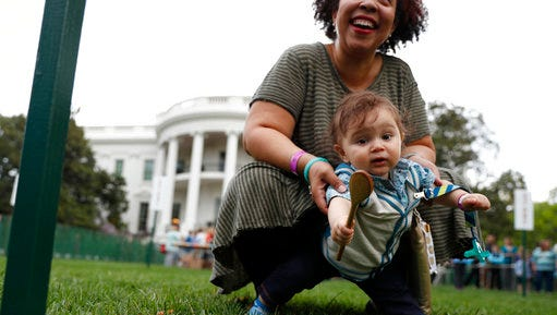 Children get a little help from parents as they cross the finish line during the White House Easter Egg Roll on the South Lawn of the White House in Washington, Monday, April,17, 2017. President Donald Trump and first lady Melania Trump are set to host the official annual Easter egg roll at the White House.