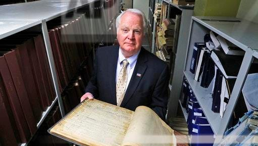 """Bernard Youngblood, Wayne County Register of Deeds, poses with an old deed registry book in Detroit, Wednesday, April 19, 2017. Youngblood recounted a case in his office, when a man came to file a quitclaim deed transferring ownership on a property. A clerk recognized the address and went to a co-worker with a question. """"Are you selling your house to that guy?"""" she asked. She wasn't. Youngblood said he faked a computer outage, leaving the would-be fraudster waiting at the counter. It bought enough time to get deputies to respond and make an arrest."""