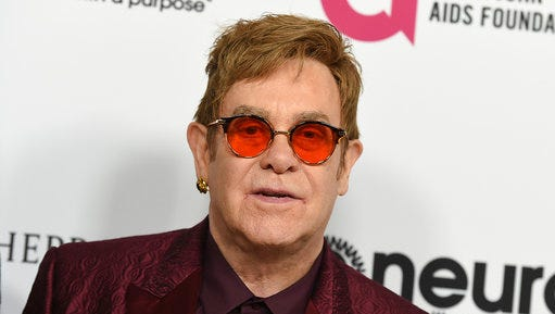 """FILE - In this March 25, 2017 file photo, Elton John arrives at Elton John's 70th Birthday and 50-Year Songwriting Partnership with Bernie Taupin celebration in Los Angeles. Elton John has cancelled more than a month of upcoming shows after contracting an """"unusual"""" bacterial infection during a South America tour that left him in intensive care for two nights. The 70-year-old performer is expected to make a full recovery and hopes to return to a stage in Twickenham, England on June 3."""