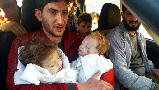"FILE -- In this Tuesday April 4, 2017 file photo, Abdel Hameed Alyousef, 29, holds his twin babies who were killed during a suspected chemical weapons attack, in Khan Sheikhoun in the northern province of Idlib, Syria. France's foreign minister says chemical analysis of samples taken from a deadly sarin gas attack in Syria shows that the nerve agent used ""bears the signature"" of President Bashar Assad's government and shows it was responsible. Jean-Marc Ayrault says France now knows ""from sure sources"" that ""the manufacturing process of the sarin that was sampled is typical of the method developed in Syrian laboratories."" But Kremlin promptly denounced the French report."