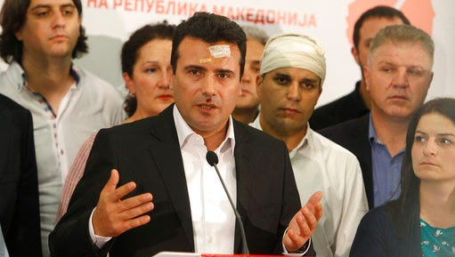 Zoran Zaev, center, leader of the Social Democrats, surrounded by party lawmakers as he talks during a news conference at the party headquarters in Skopje, Macedonia, Friday, April 28, 2017. Macedonia's opposition chief rejected the president's call for emergency party leaders' talks Friday, hours after demonstrators, mostly supporters of the country's dominant conservative party, invaded parliament.