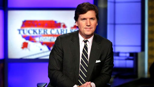 """FILE - In this March 2, 2017 file photo, Tucker Carlson, host of """"Tucker Carlson Tonight,"""" poses for photos in a Fox News Channel studio, in New York. The Fox News host and longtime conservative commentator has a two-book deal with Threshold Editions, the publisher said Tuesday, May 2.  Carlson also authored, """"Politicians, Partisans, and Parasites: My Adventures in Cable News,"""" which came out in 2003."""