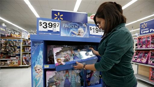 IMAGE DISTRIBUTED FOR WALMART - Walmart associate Samia Ahmed stocks the shelves for holiday shoppers with the seasons top products and gifts at the Walmart Holiday Kick-Off at Walmart Supercenter, on Friday, Oct. 31, 2014 in Plano, Texas. Starting today, customers can take advantage of 20,000 rollbacks in stores and access even more deals during a 24-hour Cyber event on walmart.com on Monday Nov. 3. (Photo by Brandon Wade/Invision for Walmart/AP Images)