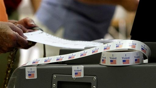 A voter slides her ballot into the machine after voting in the state's primary election Tuesday, June 3, 2014,  at Tuscaloosa Academy in Tuscaloosa, Ala. (AP Photo/Butch Dill)