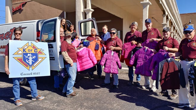 As part of the 2017 Coats for Kids of Las Cruces program, recently collected coats are delivered to Comet Cleaners on Amador Avenue. Making the delivery, in the maroon polo shirts, are, left to right, Kurt Rathgeber, Ralph Madrid, Joe Fleming, Narciso Holguin, Rick Medina, Weston Lee, Art Kershchen, Richard Hoyle and John Byers. In the blue shirt and sports coat is Comet Clearers owner Dan Schneider. In the van are Comet Cleaners employees Sandra Carrillo, left, and Felicia Jimenez.